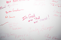 """People sign a wall after hearing Texas senator and Republican presidential candidate Ted Cruz speak to a crowd at the kick-off event at his New Hampshire campaign headquarters in Manchester, New Hampshire. One woman wrote """"In God and Ted We Trust!"""""""