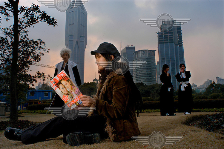 A young woman reads a fashion magazine in Renmin Gongyuan Park in Shanghai city centre..