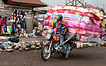 Pictured: Transporting matresses to market on a motorcycle.<br /> <br /> Goods as varied as mattresses and cabbages are precariously balanced on bikes and hauled enormous distances to be sold at market stalls.  A series of photos show workers in the Democratic Republic of Congo and neighbouring Rwanda walking up to 20 miles as they transport their wares from small villages and farms to city marketplaces.<br /> <br /> One shot even shows a man riding a motorbike with seven multi-coloured mattresses tied to the back.  Bicycles laden with sacks bursting full of potatoes will weight more than 30 stones, as workers wheel them from their homes to be sold.  SEE OUR COPY FOR DETAILS.<br /> <br /> <br /> Please byline: Joe Dordo Brnobic/Solent News<br /> <br /> © Joe Dordo Brnobic/Solent News & Photo Agency<br /> UK +44 (0) 2380 458800