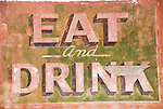 Eat and Drink sign painted on the side of an abandoned bar and grill, New Mex.