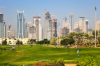 Dubai.  Skyline of Emirates Lakes Towers and Dubai Marina  overlooks the Montgomerie Golf Course at Emirates Hills.  Villa developments..