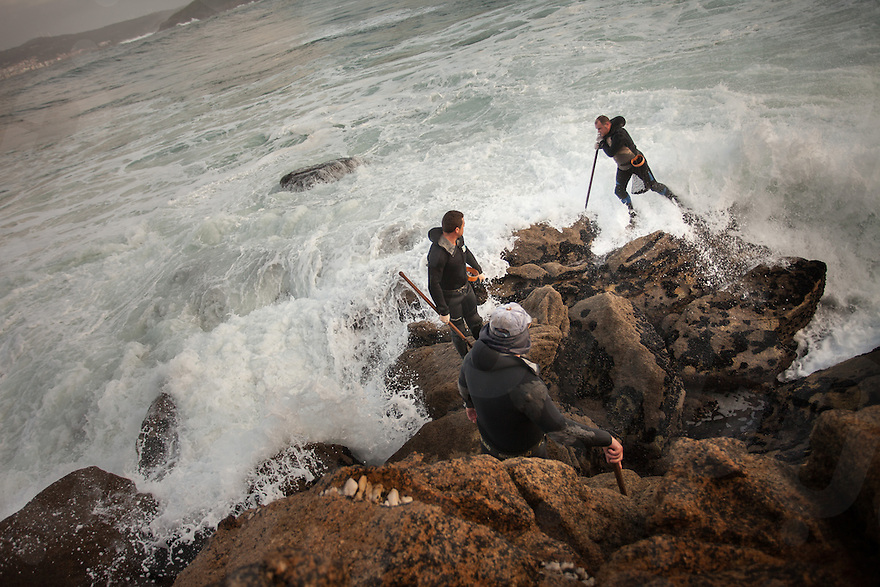 December 12, 2011 - Laxe (La Coruña). A group of percebeiros try to escape from an unexpected wave. © Thomas Cristofoletti 2011
