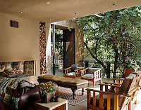 A metal framed door leads from the living area to this outdoor room which is cantilevered over the hillside