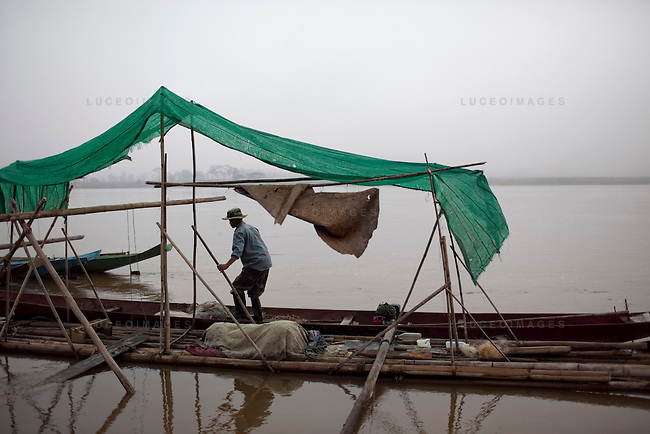 A Thai fisherman ties up his boat on the Mekong River in Sop Ruak, Thailand. Photo taken on Thursday, December 10, 2009. Kevin German / Luceo Images