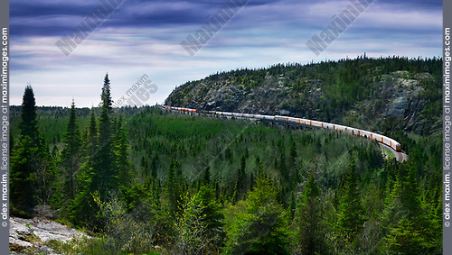 Canadian Pacific Railway, CP Rail freight train passing around a rocky hill by the shore of Lake Superior. Ontario, Canada, aerial landscape scenery.