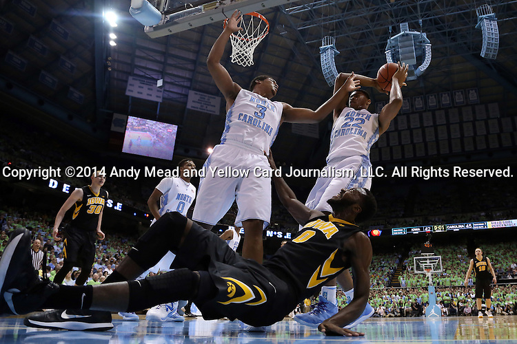 03 December 2014: Iowa's Gabriel Olaseni (ENG) (0) is fouled by North Carolina's Kennedy Meeks (3) as Isaiah Hicks (22) grabs the ball. The University of North Carolina Tar Heels played the University of Iowa Hawkeyes in an NCAA Division I Men's basketball game at the Dean E. Smith Center in Chapel Hill, North Carolina. Iowa won the game 60-55.