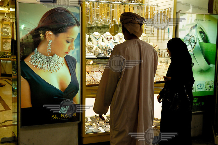 A Muslim couple look at the window display of a jewellery shop in the Gold Souk.
