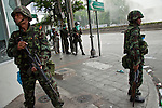 14 MAY 2010 - BANGKOK, THAILAND: Thai troops on a street corner watch upper windows for signs of anti-government protesters. Thai troops and anti government protesters clashed on Rama IV Road Friday afternoon in a series of running battles. Troops fired into the air and at protesters after protesters attacked the troops with rocket and small homemade explosives. Unlike similar confrontations in Bangkok, these protesters were not Red Shirts. Most of the protesters were residents of nearby Khlong Toei slum area, Bangkok's largest slum area. The running battle went on for at least two hours.   PHOTO BY JACK KURTZ