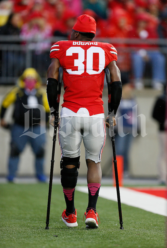 Injured Ohio State Buckeyes linebacker Devan Bogard (30) hobbles back on the field in the second half an NCAA college football game between The Ohio State Buckeyes and the Rutgers Scarlet Knights at Ohio Stadium on Saturday, October 18, 2014.  (Columbus Dispatch photo by Fred Squillante)