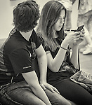 Couple sitting down, woman using her IPhone