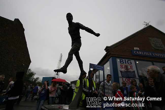 Carlisle United 1 Newcastle United 1, 21/07/2007. Brunton Park, Pre-season Friendly. Fans walking past a statue to former Carlisle United footballer Hugh McIlmoyle before their club's pre-season friendly against Newcastle United at Cumbrian's Brunton Park ground. The match ended one goal each with Newcastle equalising Livesey's opener through Nolberto Solano in the last minute. During the 2007-08 season Carlisle played in League One, English football's third tier, while Newcastle were a top Premiership team. Photo by Colin McPherson.