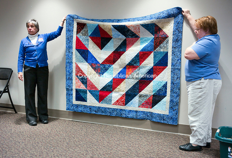 Cheshire, CT- 24 November 2015-112415CM06- Jane Dougherty, left, Co-coordinator with the Connecticut  Quilts of Valor Foundation and Carol Garrison, of Plymouth talk about a quilt at the Cheshire Library on Tuesday. Dougherty  gave a presentation about the Quilts of Valor Foundation which provides service members and veterans, touched by war with comforting quilts of valor both home and aboard.   Christopher Massa Republican-American