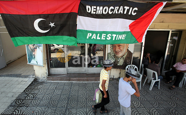 Palestinian people walk past a Libyan rebel flag in front of a shop in Gaza City, on August 24, 2011. The Hamas government and Palestinian liberation movements are reportedly showing solidarity with Libya after Libyan rebels have entered Gaddafi's house in Bab al-Aziziya compound, according to rebel sources. The claim, that the rebels entered the fortified compound through one of its gates, could not be independently verified. Al-Arabiya broadcaster however reported that the rebel flag was seen on top of the house. Photo by Ali Jadallah