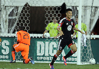 WASHINGTON, DC. - AUGUST 22, 2012:  Long Tan (27) of DC United beats  Sean Johnson (25) of the Chicago Fire for the fourth goal during an MLS match at RFK Stadium, in Washington DC,  on August 22. United won 4-2.