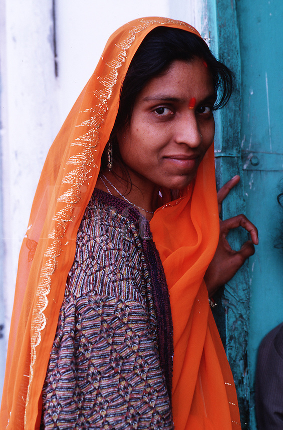 A smiling Indian woman wearing a veil poses in a doorway. Udaipur, India.
