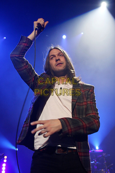 KASABIAN -Tom Meighan .Performing live at the R.A.Hall as part of the concerts in aid of Tennage Cancer Trust, Royal Albert Hall, London, England..March 27th, 2009.stage concert gig music band half length 3/4 arm in air white top jeans denim black red tartan plaid jacket grey gray .CAP/MAR.© Martin Harris/Capital Pictures.