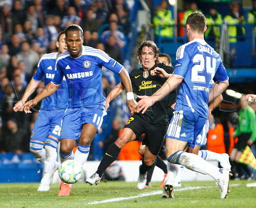 18.04.2012. Stamford Bridge, Chelsea, London. Chelsea's Ivory Coast footballer Didier Drogba and Carles Puyol of  FC Barcelona .during the Champions League Semi Final 1st  leg match between Chelsea and Barcelona  at Stamford Bridge, Stadium on April 18, 2012 in London, England.............