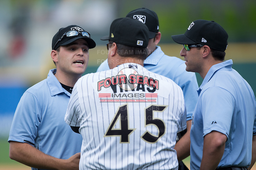 First base umpire Jansen Visconti explains a call to Charlotte Knights manager Julio Vinas (45) as umpires Ryan Additon and Derek Mollica (right) look on during the game against the Gwinnett Braves at BB&T BallPark on May 22, 2016 in Charlotte, North Carolina.  The Knights defeated the Braves 9-8 in 11 innings.  (Brian Westerholt/Four Seam Images)