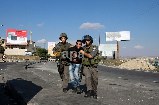 Israeli border guards arrest a Palestinian protester during clashes in the West Bank city of Nablus, on November 20, 2012. The West Bank has witnessed almost daily demonstrations in support of Gaza Palestinians who have faced a week of Israeli air strikes against militants firing rockets at the Jewish state. Photo by Nedal Eshtayah