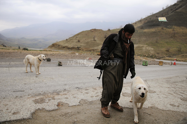 QANDIL, IRAQ:  A PKK guerrilla mans a checkpoint with dogs in the Qandil mountains...The Kurdistan Workers' Party (PKK) is a pro-Kurdish party in Turkey deemed a terrorist group by the USA and the EU.  They are based in the Qandil mountains that make up the border between Iraq and Turkey...Photo by Kamaran Najm/Metrography