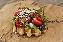 Waffle with arugula, cheese crumble, berries, Balsamic vinegar drizzle and nuts