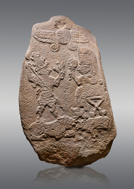 """Aslantepe Hittite relief sculpted Stele. Limestone, Aslantepe, Malatya, 1200-700 B.C. Anatolian Civilisations Museum, Ankara, Turkey.<br /> <br /> Under the winged sun disk, is a god standing on a lion and across the god is a sitting goddess. The hieroglyphs reads """"Karhuhas, the stag god"""" for the god, and """"Kubaba"""" for the Goddess. <br /> <br /> Against a gray background."""