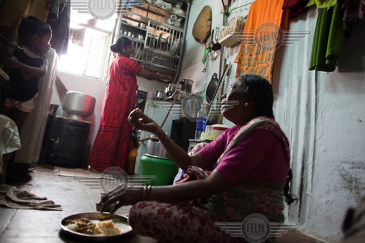 People in the family home, a single small room that sleeps five, in Dharavi slum.