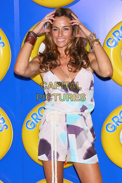 "KELLY BENSIMON.The New York Premiere of ""Grown Ups"" at the Ziegfeld Theater, New York, NY, USA..June 23rd, 2010.half length pink purple white dress sash hands bracelets gold brown cuff pattern.CAP/LNC/TOM.©TOM/LNC/Capital Pictures."