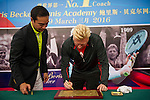 Mission Hills Vice Chairman Tenniel Chu (left) helps tennis legend Boris Becker (right) to sign his name under his handprint on clay during the press conference for the opening of Boris Becker Tennis Academy at Mission Hills Resort on 19 March 2016, in Shenzhen, China. Photo by Lucas Schifres / Power Sport Images