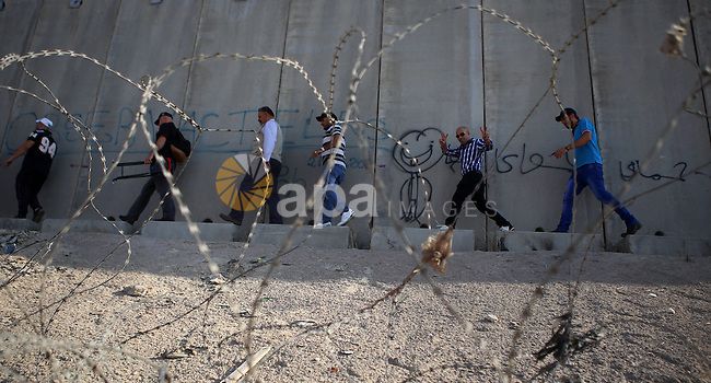 Palestinian men cross a section of Israel's separation barrier near Qalandia checkpoint between Ramallah and Jerusalem, to enter Jerusalem to attend Laylat Al-Qadr, also known as the Night of Power, during the Holy month of Ramadan, on July 13, 2015. Photo by Shadi Hatem