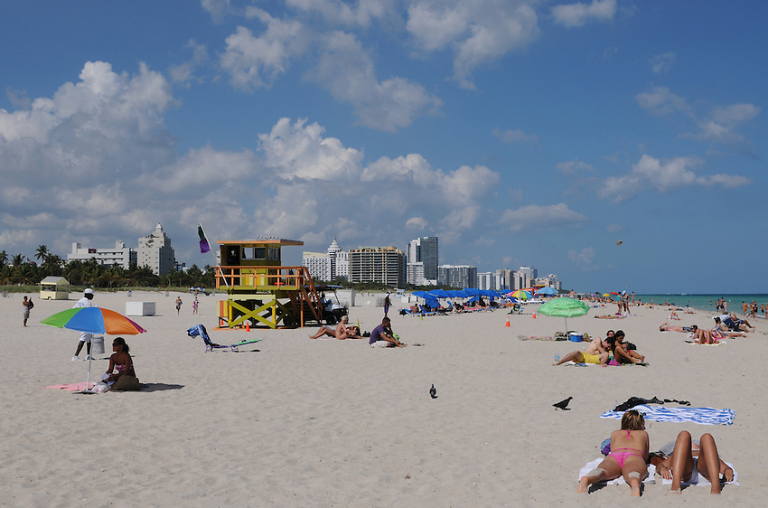 People enyoying the sun sand and warm ocean waters of beautiful Miami Beach Florida.