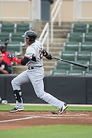 Ronald Guzman (20) of the Hickory Crawdads follows through on his swing against the Kannapolis Intimidators at CMC-Northeast Stadium on April 17, 2015 in Kannapolis, North Carolina.  The Crawdads defeated the Intimidators 9-5 in game one of a double-header.  (Brian Westerholt/Four Seam Images)
