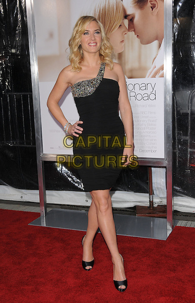 """KATE WINSLET .World Premiere of """"Revolutionary Road"""" held at The Mann Village Theatre in Westwood, California, USA. .December 15th, 2008 .full length dress black jewel encrusted one shoulder open toe christian louboutin shoes heels hand on hip .CAP/DVS.©Debbie VanStory/Capital Pictures."""