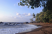 Marenco, Costa Rica. Idyllic sandy beach with palm trees, deciduous trees, rocks in the evening light.