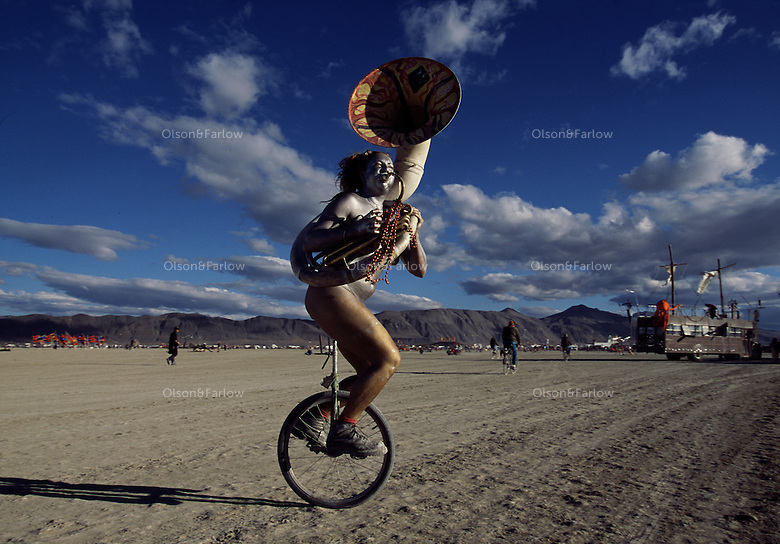 "Wearing a smile and a sousaphone, Erin ""Red"" Thompson makes music in a balancing act during the annual Burning Man artfest in Nevada's Black Rock Playa. Silver-painted Thompson was like a mirage and disappeared into the crowd on her unicycle. ""There are no spectators,"" says Red, ""only participants.""  The counter-culture celebration is held in the desert annually."