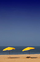Two beach umbrellas sit on beach
