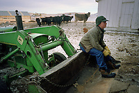 Joe Kennedy, 13, the lone student at Cozy Hollow Elementary School on the Kennedy ranch in Wyoming, waits atop a tractor before working cattle with his father, grandfather and uncles. Wyoming, one of the nation's most rural states, supports many isolated schools with few students. (Kevin Moloney for the New York Times)