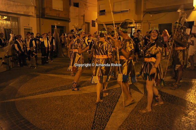 "Members of the ""penya,"" or group of friends calling themselves ""Els Kutos,"" or ""the pigs"" in Catalan, dance in the main square in their Native American attire for Costume Night celebrations during the municipal fiestas in the town of Costur, Spain on August 17, 2009."
