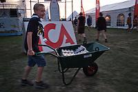 A young Scout in the Planning Team who is at the Jamboree with his parents is delivering chilled soft drinks.