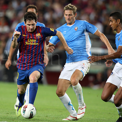 17.08.2011 Barcelona, Spain. La Liga Football.  FC Barcelona versus Osasuna.  Barcelona's lionel Messi controls the ball passed through Osasuna's Ruben and Roversio