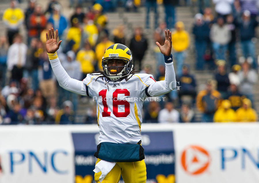Michigan quarterback Denard Robinson (16) holds his arms up celebrating a touchdown pass during the Wolverines' spring football game, Saturday, April 17, 2010, in Ann Arbor, Mich. (AP Photo/Tony Ding)