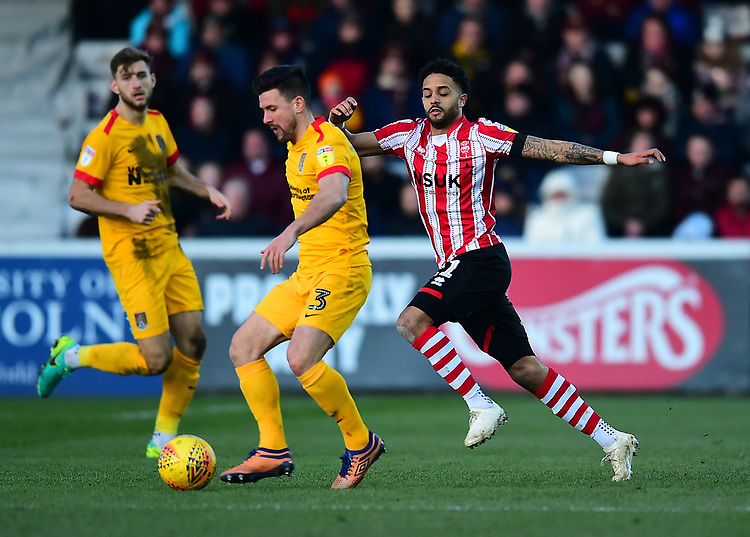 Northampton Town's David Buchanan under pressure from Lincoln City's Bruno Andrade<br /> <br /> Photographer Andrew Vaughan/CameraSport<br /> <br /> The EFL Sky Bet League Two - Lincoln City v Northampton Town - Saturday 9th February 2019 - Sincil Bank - Lincoln<br /> <br /> World Copyright &copy; 2019 CameraSport. All rights reserved. 43 Linden Ave. Countesthorpe. Leicester. England. LE8 5PG - Tel: +44 (0) 116 277 4147 - admin@camerasport.com - www.camerasport.com