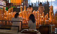 Attendants wearing the all-white outfits which are required for this festival keep alight the many giant candles at the 200 year old San Jao Sien Khong Chinese Shrine in Bangkok during the ten day Buddhist-Taoist Vegetarian Festival which is intended to purge meat and other heating foods from the body.