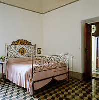 A geometric pattern is created by the floor tiles in this bedroom which is furnished with an antique wrought-iron bed