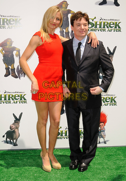 "CAMERON DIAZ & MIKE MYERS .at DreamWorks Animation's ""Shrek Forever After"" L.A. Film Premiere held at Gibson Amphitheatre at Universal CityWalk, Universal City, California, USA, May 16th, 2010. .arrivals full length red sleeveless dress mini beige nude suede shoes black suit tie blue grey gray shirt arm around .CAP/ROT.©Lee Roth/Capital Pictures"