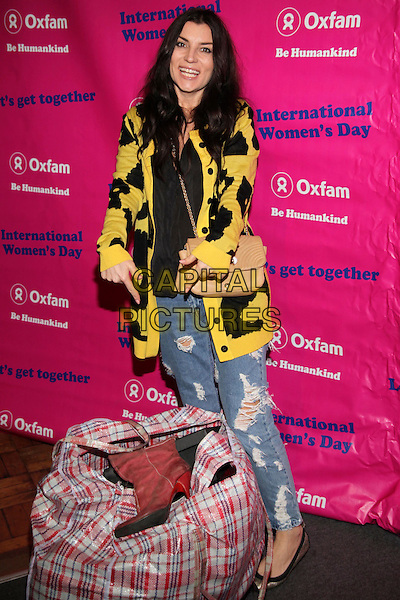 Grace Woodward.Celebrity jumble sale in aid of Oxfam, London, England..February 26th, 2012.full length bag donation jeans denim black yellow cardigan beige bag purse .CAP/JEZ  .©Jez/Capital Pictures.