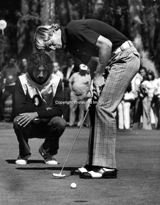 PGA golfer Johnny Miller putting with his caddy Andy Martinez behind him. (1974 photo/Ron Riesterer)