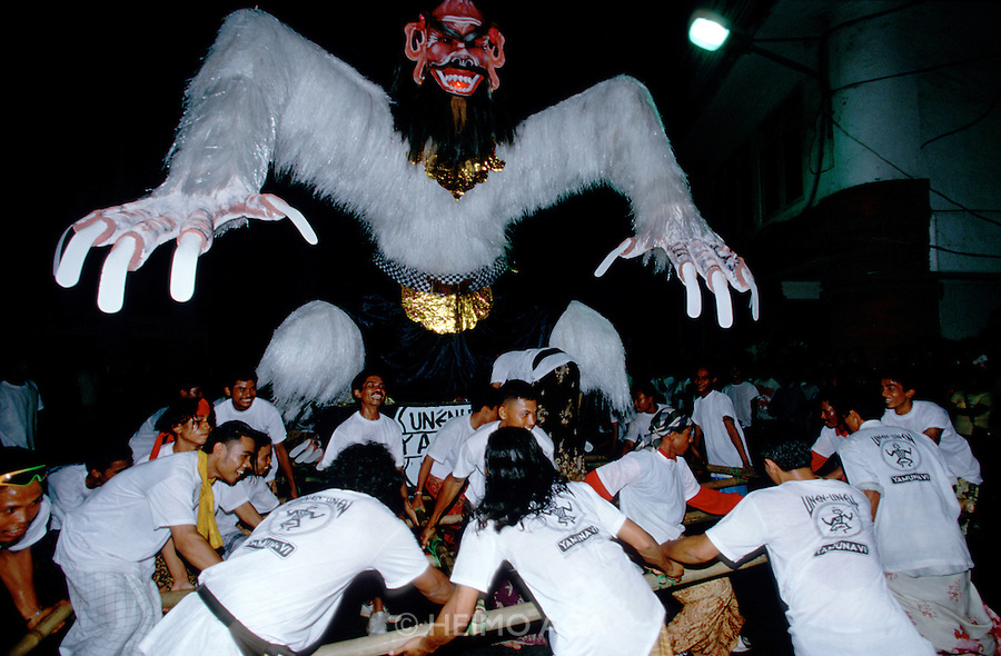 """Eve of Nyepi (Balinese New Year) Festival..An """"Ogoh-Ogoh"""" being carried in the big parade...On Nyepi day, evil spirits descend to see wether the island is inhabited by humans. That's why nobody is allowed to leave the house on that day: when the demons don't find anyone, they leave the island alone for another year. Tourists are confined to their hotels, the use of cars is forbidden and, since 2000, even international air traffic is banned..On the eve of Nyepi however, a great """"Pratima"""" (town meeting) is held on Denpasar's Puputan Square, complete with Hindu rituals and offerings to the gods. After sunset, huge cardboard monster puppets called """"Ogoh-Ogoh"""" mounted on bamboo grids are carried in a loud and vivid parade around town by groups of young men, before they are burnt."""