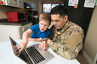 Military dad and son doing homework in kitchen