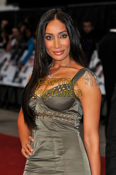 SOFIA HAYAT .'Knight and Day' UK film premiere at the Odeon cinema, Leicester Square, london England 22nd July 2010.half length dress hand on hip epaulettes chains tassels grey gray green khaki lace-up rivets cleavage silver necklace .CAP/PL.©Phil Loftus/Capital Pictures.